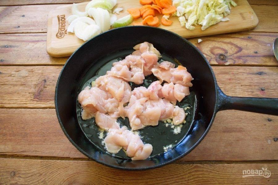 Овощи очистите и нарежьте произвольно. Капусту измельчите тонкой соломкой, лук и морковь я нарезала полукольцами. Чеснок очистите и нарежьте мелко. На двух видах масла обжарьте чеснок. Куриное филе нарежьте кусочками. Выложите филе на сковороду и обжарьте.