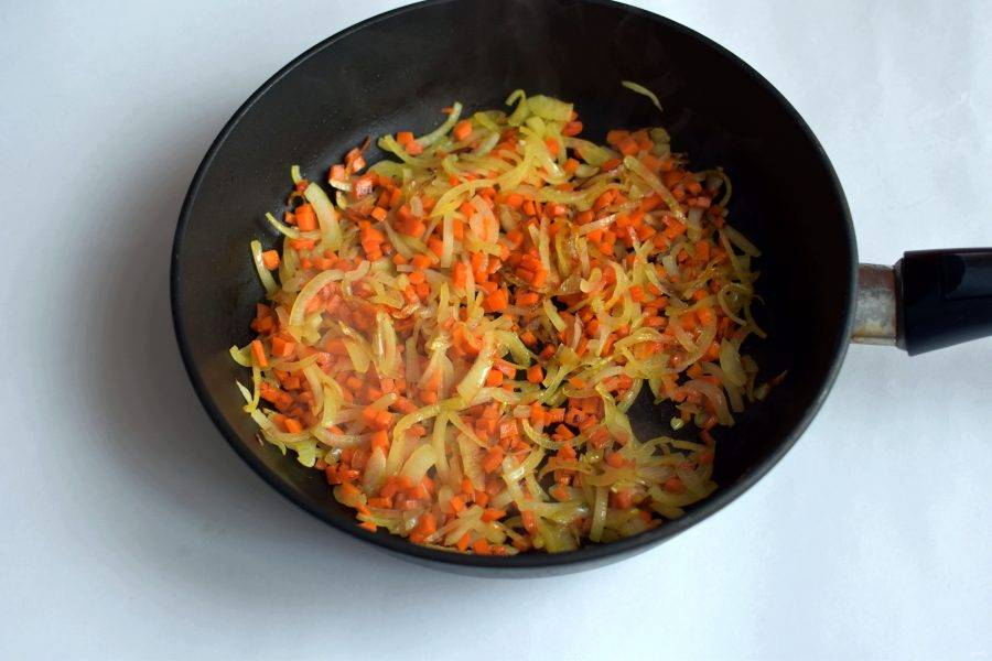 В сотейнике разогрейте масло и обжарьте мелко нашинкованные лук и морковь до легкой позолоты.