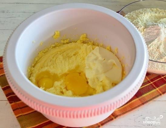 Сливочное масло достаньте из холодильника, дайте ему подтаять. Затем поместите масло в миску. Добавьте к нему сахарный песок и ванилин. Добавьте сметанку, вбейте сырые куриные яйца. Тщательно все перемешайте.