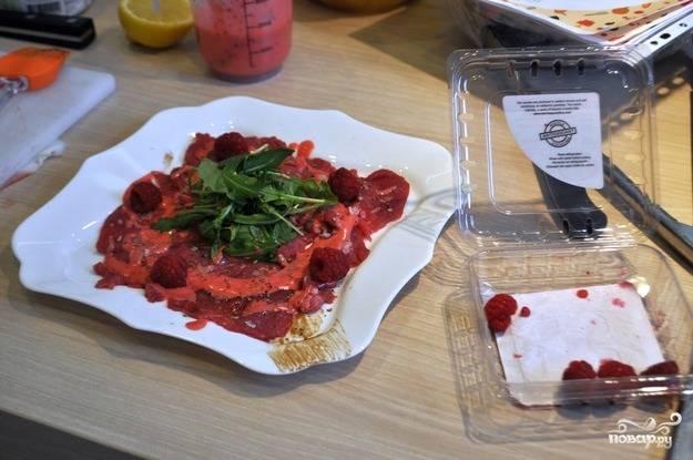 Рукколу промойте и смешайте с соусом песто. Мясо полейте малиновым соусом и украсьте ягодами малины, сверху выложите рукколу, поперчите и посолите по вкусу.