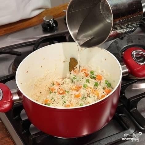 Добавьте 600 мл воды. Посолите, накройте крышкой и варите до готовности риса на среднем огне.