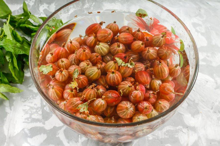 Крыжовник промойте в воде, удалите листочки и хвостики с каждой ягоды.
