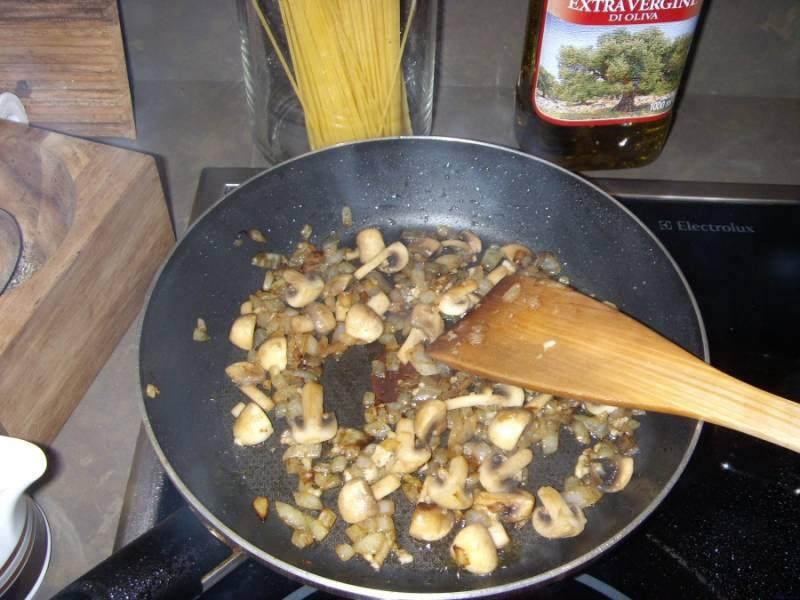 Добавляем грибы, обжариваем несколько минут. Также кладем раздавленный чеснок.
