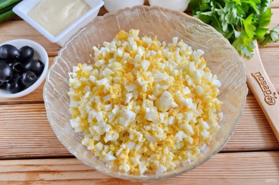 Очистите яйца от скорлупы, порежьте маленькими кубиками.