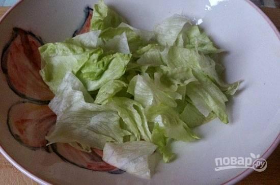 Выкладываем на тарелку листья салата.