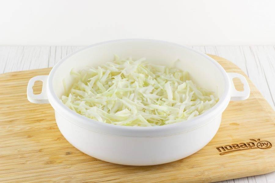 Капусту мелко нашинкуйте, добавьте свежемолотый перец, щепотку сахара и соли, помните руками.