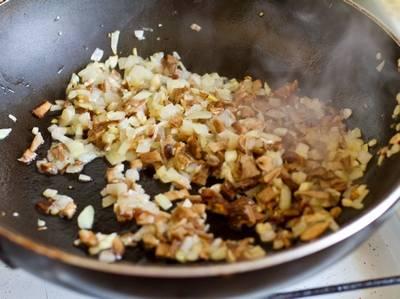 Лук и грибы мелко нарежьте и обжарьте на растительном масле до золотистого цвета. Соль и перец добавьте по вкусу. Дайте начинке остыть, затем измельчите все в крошку при помощи блендера.