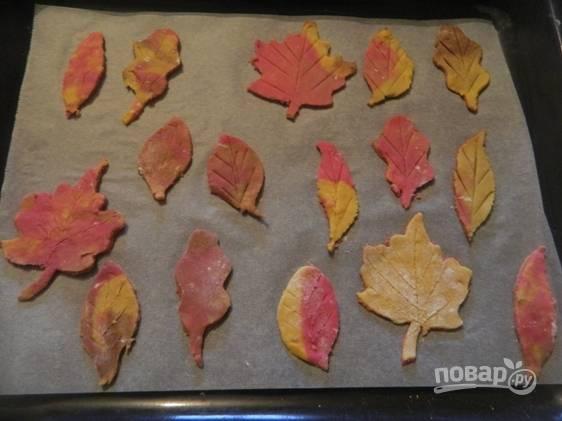 Затем вырезаем осенние листики формочкой или с помощью бумажного трафарета. Выкладываем листья на противень, застеленный пергаментом.