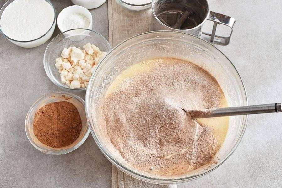 Просейте сверху смесь муки, разрыхлителя и 3 столовых ложки какао-порошка.