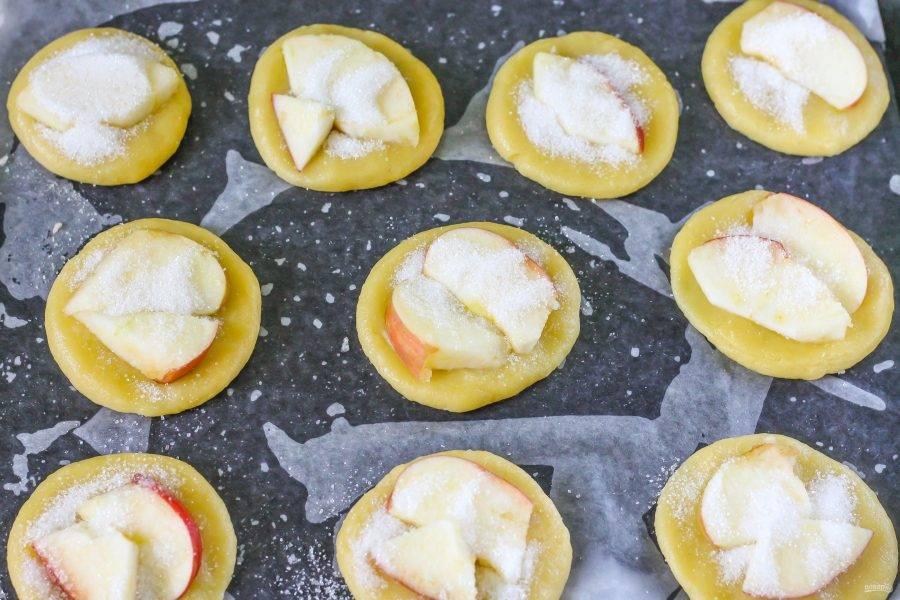 Яблоко промойте в воде, очистите от семян, нарезав на четвертинки, затем нарежьте ломтиками. Расплющите клубочки теста в лепешки, но не тонкие, выложите на каждую из них ломтики яблока и присыпьте оставшимся сахарным песком. Поместите противень в духовку и испеките печенье в течение 20-25 минут до румяности.