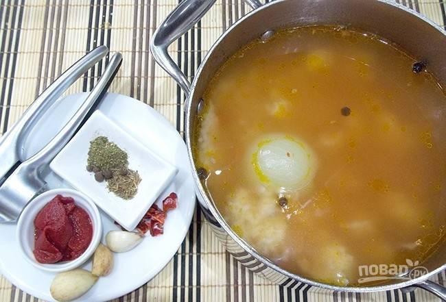 Продолжайте варить харчо на небольшом огне. Добавьте в него пропущенный через пресс чеснок, томатную пасту, измельчённый острый перец, кориандр и хмели-сунели.