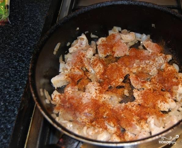 Куриное филе вымойте и обсушите. Нарежьте его на равные куски и обжарьте на раскаленной сковородке на растительном масле вместе с измельченным репчатым луком и зубчиками чеснока, посыпав специями и солью.