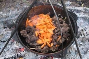 Добавьте в казан нарезанную брусочками морковь. Перемешайте и тушите еще 10 минут.