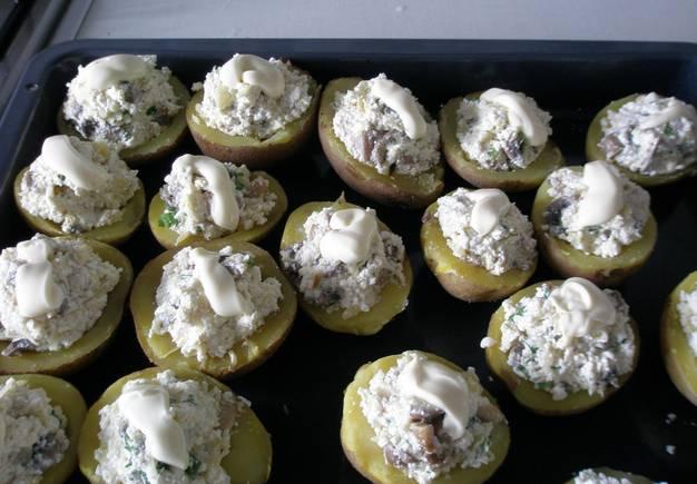 Картофель фаршируем начинкой и выкладываем на противень, смазанный маслом. Сверху можно капнуть еще немного майонеза. Запекаем блюдо в духовке 25 минут, температура 220 градусов.
