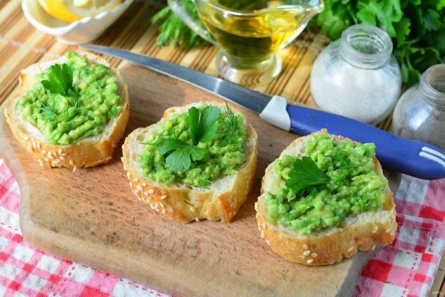 Намажьте бутерброды смесью из авокадо и чеснока. Украсьте зеленью по вкусу и сразу подавайте к столу.