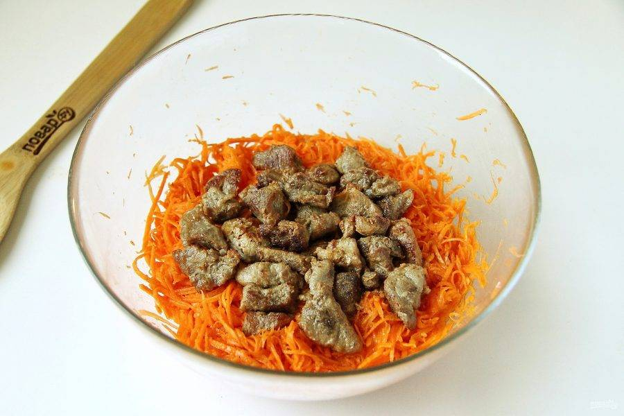 Обжаренные кусочки мяса вместе с раскаленным маслом добавьте к моркови и интенсивно перемешайте.