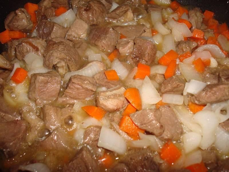 Теперь наливаем на сковородку растительное масло и обжариваем на сильном огне баранину со всех сторон до золотистого цвета. Потом добавляем к мясу нарезанную морковь и репчатый лук, жарим все еще пару минут, затем перекладываем баранину с овощами на дно горшочка, посыпаем все солью и молотым перцем.