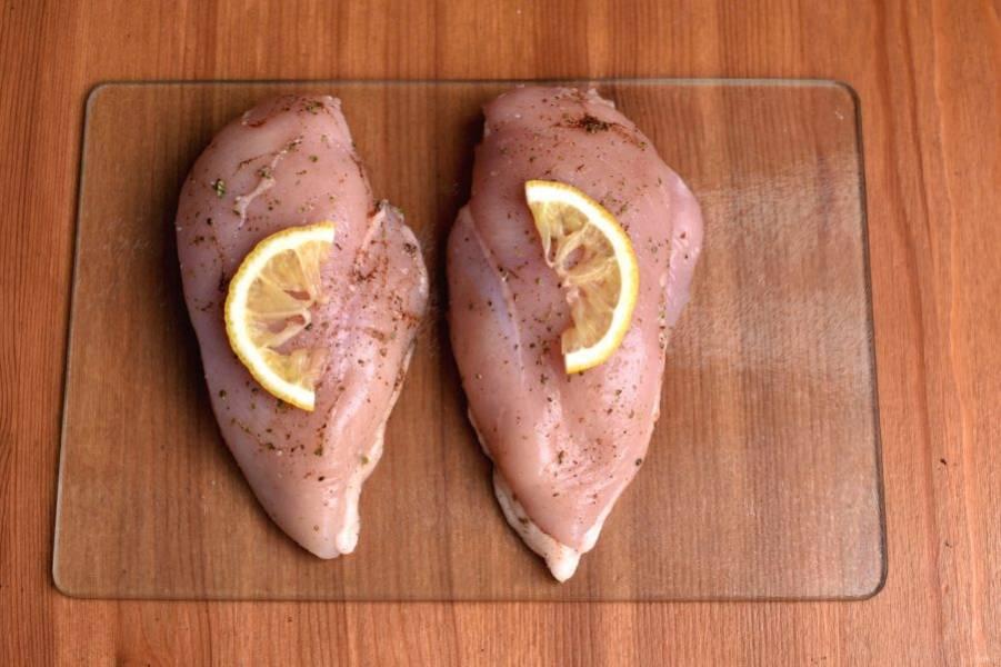 Куриную грудку разделайте на филе и натрите пряностями и специями. Втирайте руками со всех сторон. Тонкий ломтик лимона разрежьте пополам и выложите сверху на филе.