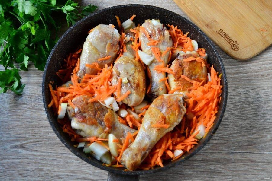 Когда голени обжарятся, отправьте в сковороду лук и морковь, добавьте соль и специи. Перемешайте и обжарьте в течение 5 минут, чтобы овощи слегка отмякли.