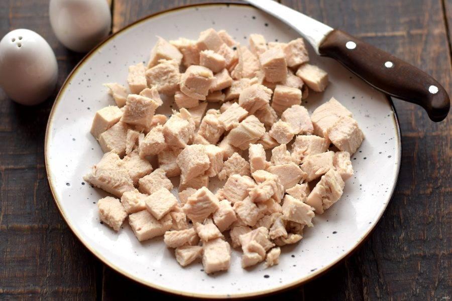 Куриное филе заранее отварите в подсоленной воде до готовности. Примерное время варки составляет 15 минут после кипения жидкости. Отварное мясо полностью остудите, нарежьте на средние кубики и полоски.