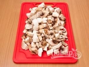 Лук почистите, грибы промойте. Нарежьте эти ингредиенты мелкими кусочками.