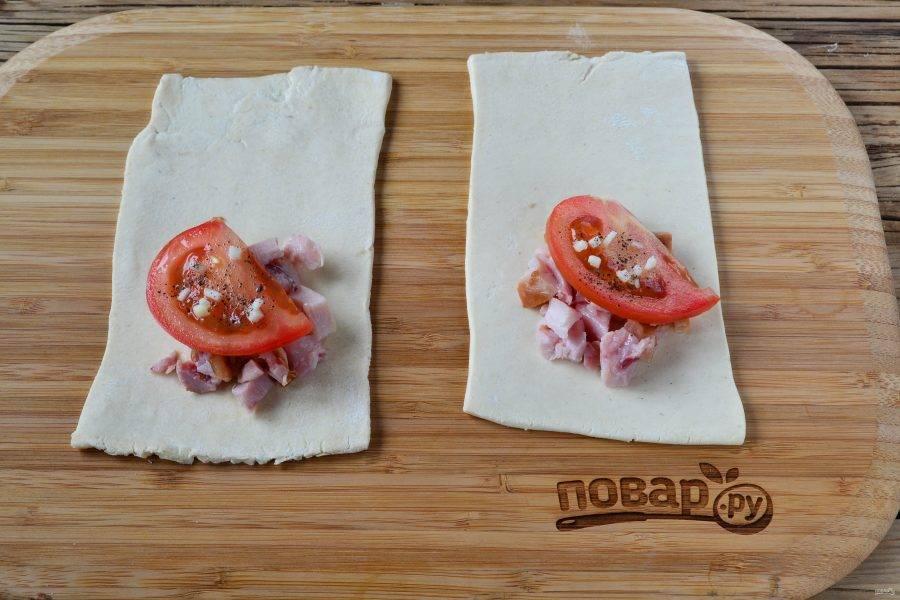 Условно поделите прямоугольник пополам, на одну половину положите горсть куриного мяса, затем положите кружочек или половину кружочка помидора, сверху положите мелко порезанный чеснок, слегка присыпьте перцем и по желанию солью. Сбрызните оливковым маслом.