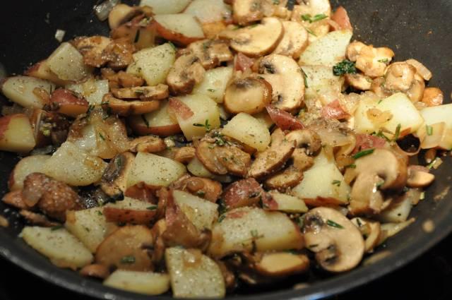 3. На отдельной сковороде разогреть масло и отправить туда измельченный лук. Грибы вымыть и нарезать тонкими ломтиками. Добавить к луку и жарить минут 5. Очистить картофель и нарезать небольшими кусочками. Отправить на сковороду к грибам и жарить вместе до готовности, посолив и поперчив по вкусу. Также можно добавить любимую зелень по вкусу.