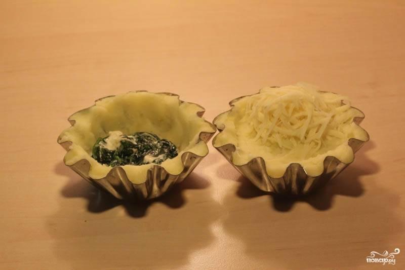 Формочки смажьте маслом. Уложите 2/3 пюре, сверху шпинат и оставшееся пюре. Посыпьте сыром.