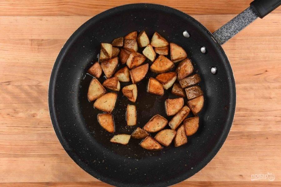 2. После этого в разогретом масле обжарьте картофель 5 минут, а потом переставьте сковороду в духовку на 23 минуты при 200 градусах. Затем добавьте соль и перец, перемешайте.