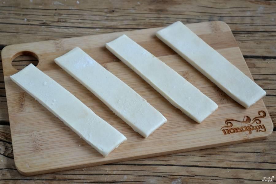 Тесто порежьте на полоски шириной около 2 см. Посыпьте их смесью корицы и сахара.