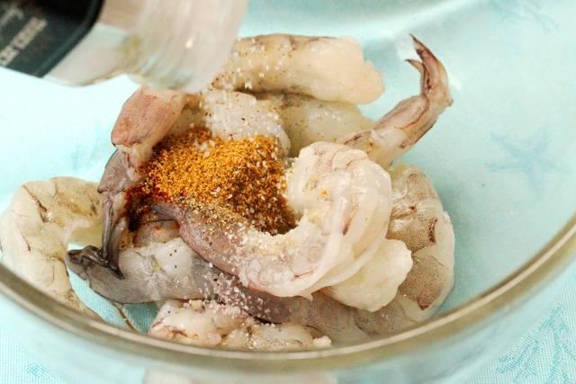 1. Свежие креветки нужно промыть как следует под проточной водой и обсушить бумажной салфеткой. Всыпать щепотку зиры, чили, сушеного чеснока, соли и перца.