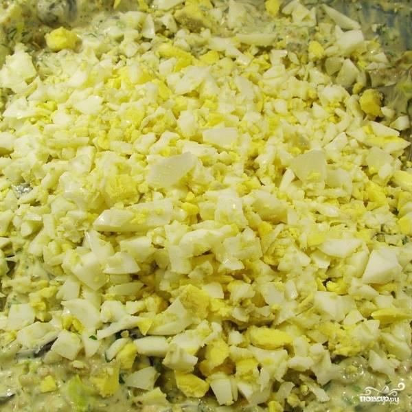 Тем временем мелко нарезаем и смешиваем в салатнице яйца, бекон, маслины, сельдерей, маринованные огурцы, зеленый лук и укроп.
