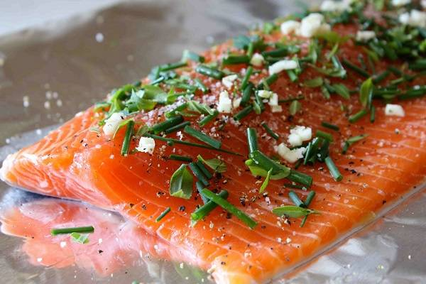 3. Рыбку необходимо посолить и поперчить по вкусу. Лучше всего использовать крупную соль и свежемолотый перец (можно смесь перцев). Чеснок очистить, пропустить через пресс или измельчить ножом. Смесью чеснока и зелени натереть семгу.