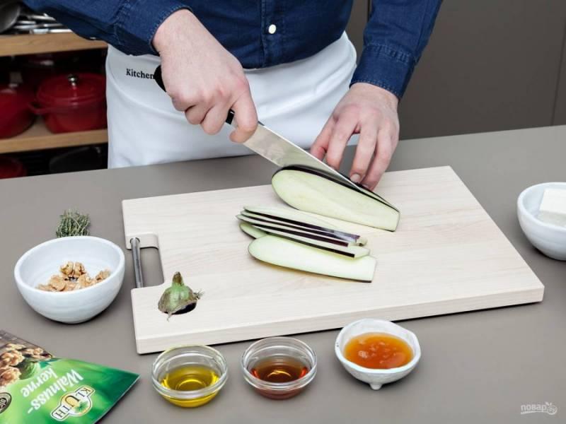 1. Нарежьте тонкими кусочками во всю длину баклажан. Выложите их на противень. Добавьте масло и соль. Отправьте запекаться на 20 минут при 220 градусах.