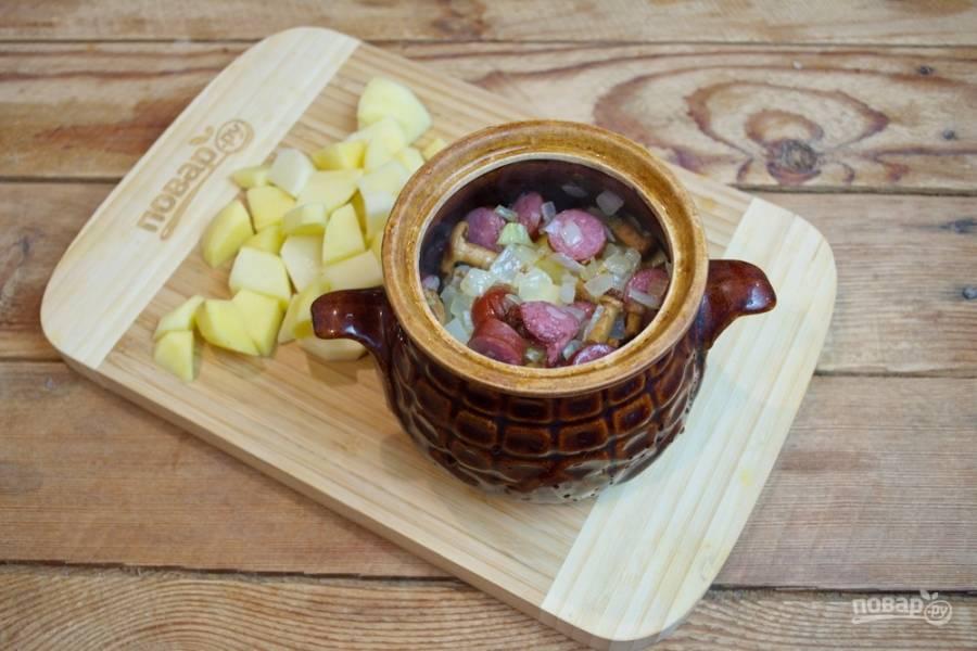 3-4 ст. ложки колбасной зажарки выложите в каждый горшочек.