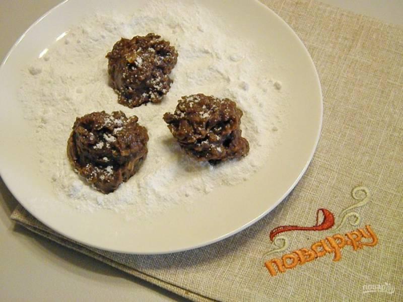 3. На тарелочку насыпьте сахарную пудру, чайной ложкой набирайте массу для формования и обваливайте шарики в пудре, формируя круглые или овальные печенюшки.