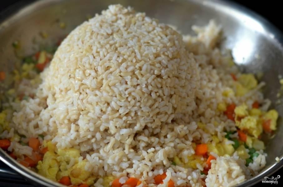 4. Следующим этапом добавьте на сковороду отварной рис. Аккуратно все перемешайте. По вкусу можно влить соевый соус, добавить любимые специи, чтобы сделать рис с морковкой и луком на сковороде в домашних условиях еще ароматнее.