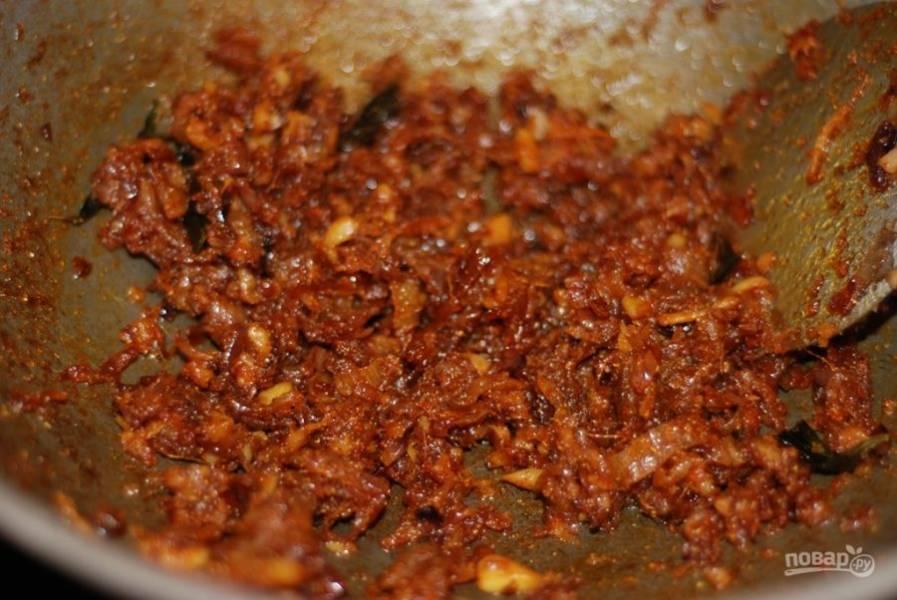2.  Убавьте огонь до минимума. Насыпьте немного приправы: карри, куркумы, кориандра, соли и молотого перца. В это время подготовьте цыпленка. Смешайте оставшиеся специи куркумы, имбиря, чили, кориандра, соли и перца и замаринуйте кусочки мяса.