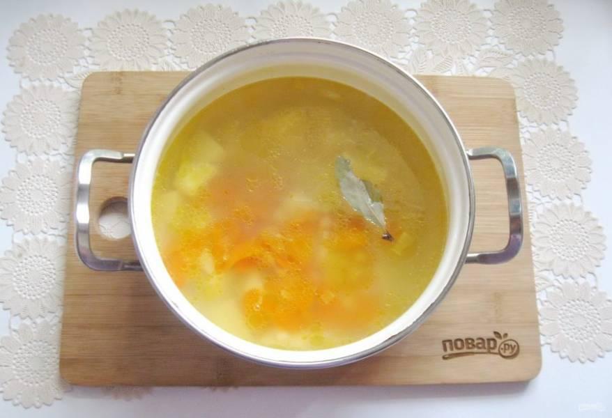 Выложите в суп лавровый лист, посолите и поперчите по вкусу.
