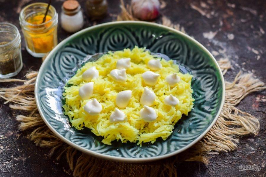 Картофель натрите на мелкой терке, выложите в салат первым слоем, посолите немного и смажьте майонезом.