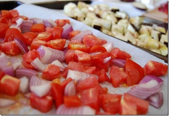 3. То же самое проделайте с помидорами и луком - порежьте кубиками и дольками, по размеру схожими с баклажаном, выложите в миску, туда же отправьте очищенные зубчики чеснока (не режьте их), сбрызните маслом, посыпьте солью и перцем и перемешайте. Выложите на другой противень, застеленный пергаментом.