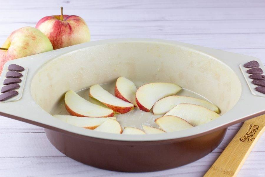 Форму (22-24 см) смажьте растительным маслом, можно слегка припудрить мукой. Яблоки помойте, очистите от сердцевины, нарежьте дольками 3-4 мм толщиной и выложите на дно формы.