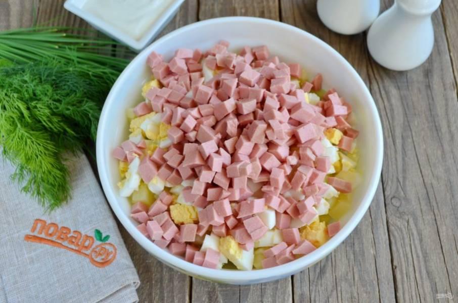 Колбасу порежьте кубиками, размер всех составляющих окрошки должен быть одинаковым.