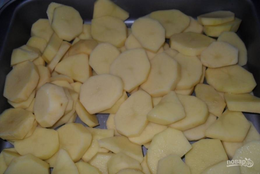 Противень смажьте маслом. Картофель помойте, почистите и нарежьте кольцами. Распределите их по противню.