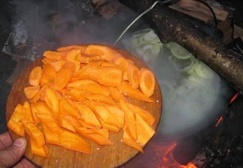 После закипания воды уберите всю пену с казана и добавьте в него лук с морковкой.