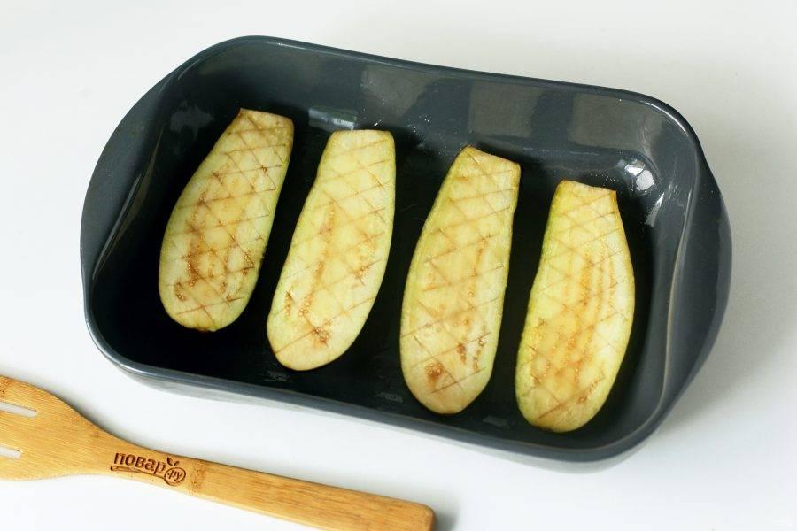 Баклажаны разрежьте вдоль на две части, сделайте надрезы ножом, смажьте маслом и отправьте запекаться в духовке при температуре 200 градусов около 20 минут или до готовности.