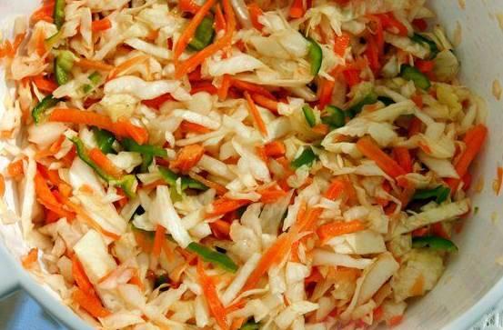 2. Пока баклажаны остывают, сделаем начинку. Мелко нашинкуем капусту и морковь, перец порежем полосочками, чеснок измельчим. Перемешаем, добавим специи. Оставим постоять.