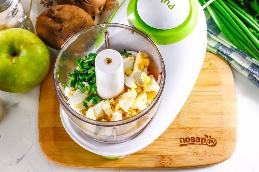 Куриные яйца очистите от скорлупы, промойте в воде и нарежьте мелким кубиком. Промойте и измельчите зеленый лук. Добавьте обе нарезки в чашу измельчителя либо прокрутите через мясорубку.