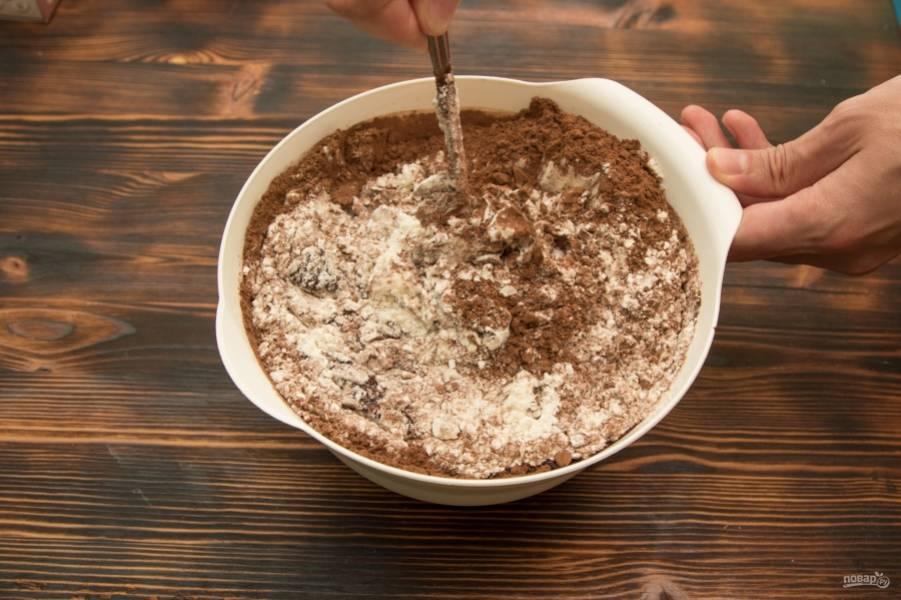 Добавим в яично-шоколадную массу муку и какао, перемешиваем до однородности массы лопаткой или ложкой.