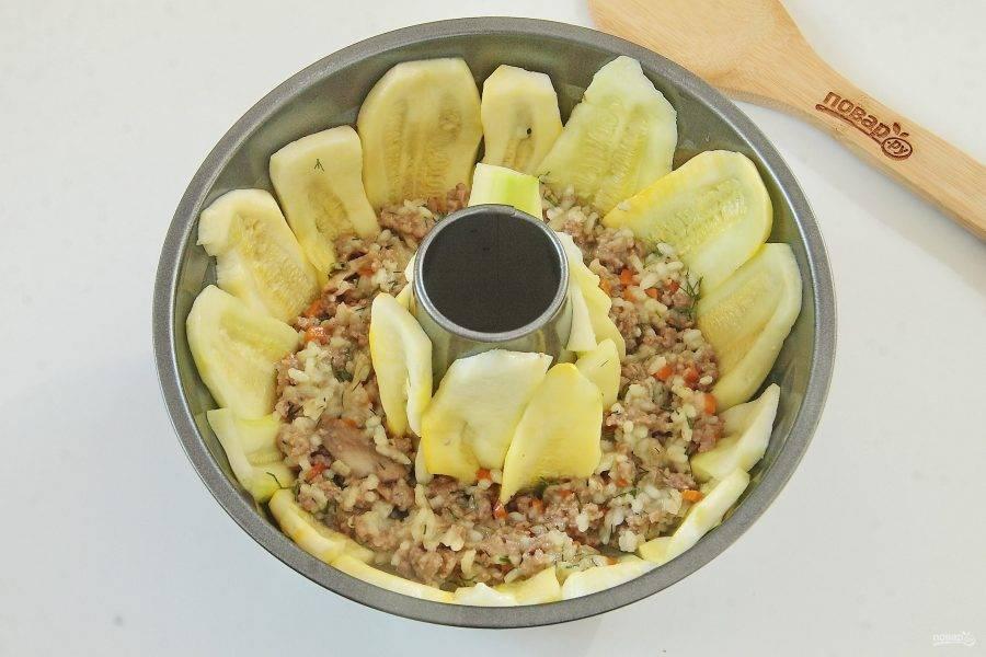 Кабачки уложите в смазанную маслом форму, смазанной яйцом стороной вверх. Кабачки укладываем таким образом, чтобы пластины закрывали весь объем формы. Сверху на кабачки начинаем выкладывать начинку.